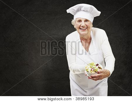 senior woman cook holding a bowl with salad against a grunge background