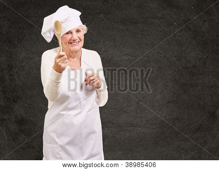 portrait of senior cook woman holding a wooden spoon against a grunge wall