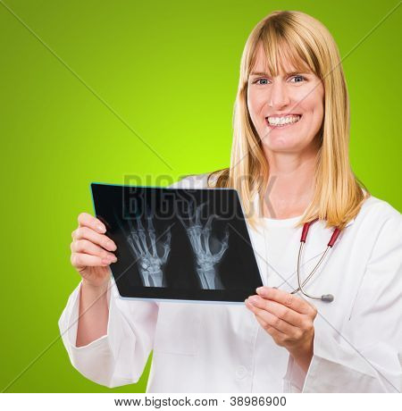 Portrait Of Happy Doctor Holding X-ray against a green background