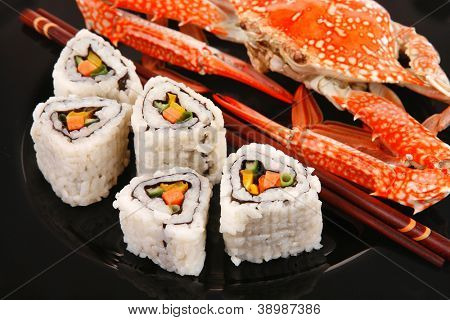 Sushi Maki Roll with Vegetables and Salmon inside . on black dish with boiled crab . Japanese Cuisine