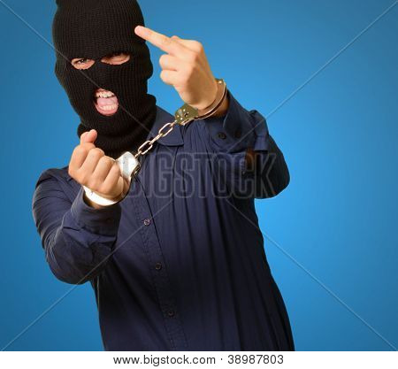 angry criminal man locked in handcuffs isolated on blue background
