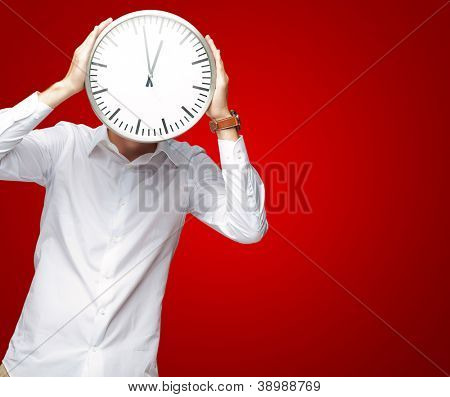 Young Man Holding Big Clock Covering His Face On Red Background