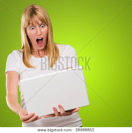 Shocked Woman Looking At Laptop against a green background