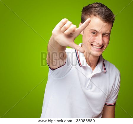 Portrait Of A Handsome Young Man Gesturing On Green Background