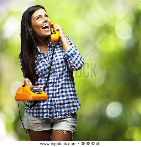 portrait of young woman talking on vintage telephone against a nature background