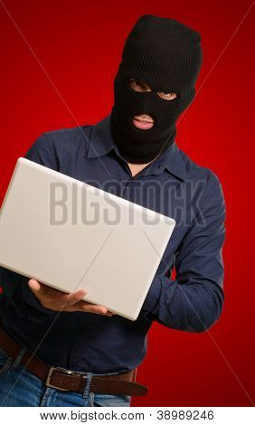 young male thief holding laptop isolated on red background