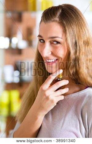 Young woman buying perfume in a shop or store, testing the fragrance on the neck