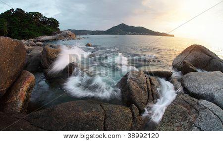 Rocky coast of Andaman sea near Laem Sing beach at sunset light. Phuket, Thailand