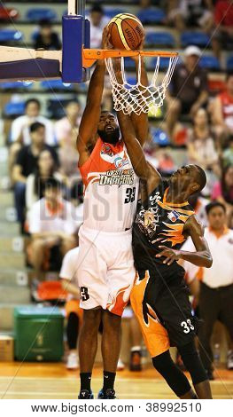 KUALA LUMPUR - OCTOBER 28: Dragons' Moala Tautaa (white) scores against Firehorse's Devon Sullivan (black) in a Malaysia National Basketball League match on October 28, 2012 in Kuala Lumpur, Malaysia.
