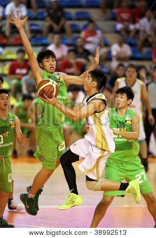 KUALA LUMPUR - OCT 28: Farmcochem's Wee Chuan Chin (white) leaps towards the hoop in a Malaysia National Basketball League match against Crouching Tiger on October 28, 2012 in Kuala Lumpur, Malaysia.