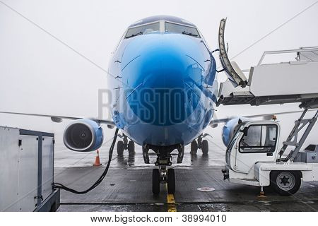 refueling a plane on the airport, bad weather and fog