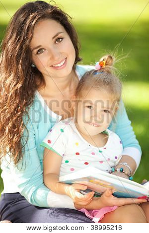 Mother with daughter reading a book in the park