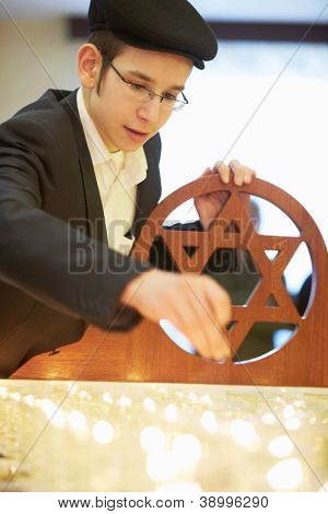 MOSCOW - JAN 27: Young jewish boy lighting funeral candle in Moscow synagogue Beis Menachem  in International Holocaust Remembrance Day, Jan 27, 2012, Moscow, Russia.