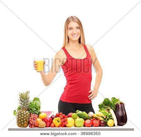Female athlete refreshing with juice after exercise, behind a table full of healthy food isolated on white background