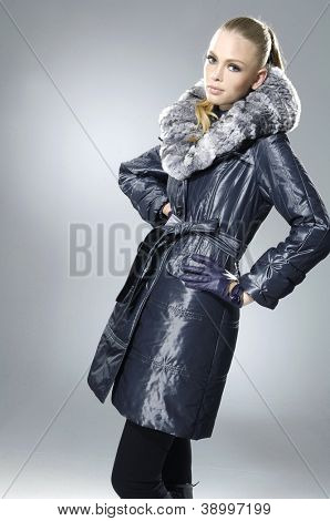 fashion model in fur coat clothes posing on light background