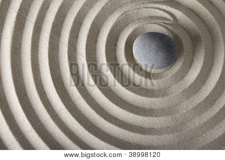 concentration and spirituality in Japanese zen garden spa background with stone and circles in sand concept for meditation and relaxation