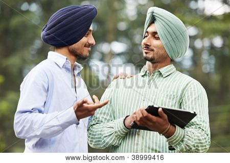 Two smiling authentic native indian punjabi sikh men in turban discussing something with tablet computer