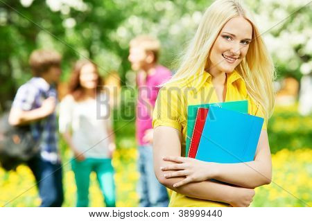 One happy smiling student girl with note books and workbooks in spring outdoors