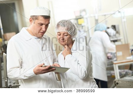 Two pharmaceutical workers discussing manufacture project with tablet computer at pharmacy industry