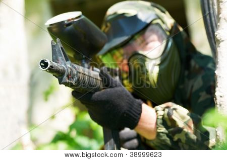paintball sport player in protective uniform and mask aiming and shooting with gun outdoors. Shallow DOF