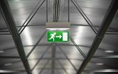 green emergency exit sign in public building