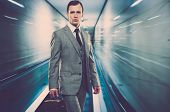 pic of escalator  - Man in classic grey suit with briefcase standing on escalator - JPG