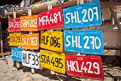 Traditional handcrafted vehicle registration plates like souvenirs for sale in Trinidad, Cuba. poster
