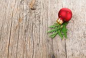 picture of shaky  - Red Christmas ball on wooden background with green thuja branch - JPG