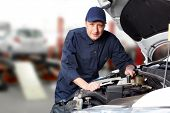 stock photo of grease  - Car mechanic working in auto repair service - JPG