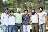 Group portrait of smiling authentic native indian punjabi sikh men in turban with bushy beard