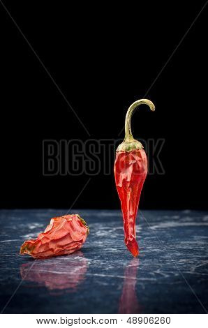 Two spicy chili peppers with reflection