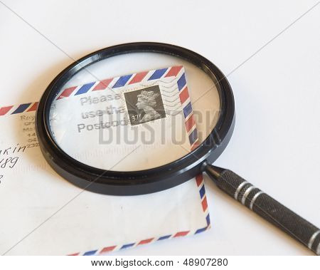 Magnifying Glass On An Envelope With A Postage Stamp