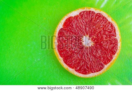 Fresh grapefruit on green background