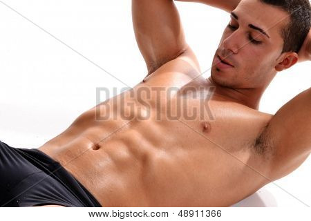 Man athlete doing fitness, abdominal exercises. White background. Studio shot.