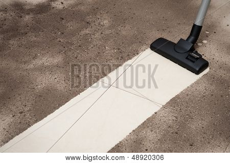Vacuum cleaning dirt on a tiled floor