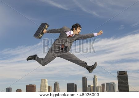 Side view of a young businessman running with briefcase in midair above city