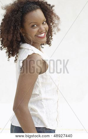 Portrait of a smiling African American woman with curly hair standing against white background