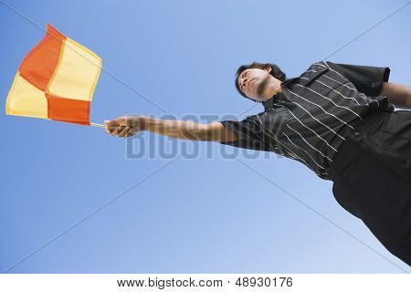 Low angle view of a soccer linesman waving flag against clear blue sky