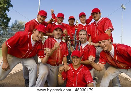 Portrait of excited baseball team holding trophy with pride