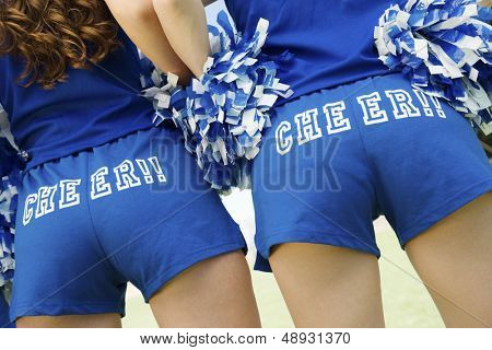 Closeup rear view midsection of two cheerleaders holding pom poms
