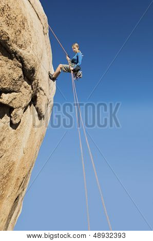 Low angle view of a young woman rappelling from cliff against clear blue sky