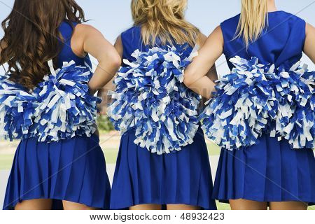Rear view midsection of three cheerleaders holding pom poms