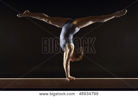 Side view of a female gymnast doing split handstand on balance beam against black background
