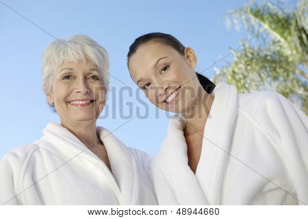 Portrait of two multiethnic women in bathrobes against blue sky at spa