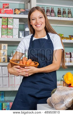 Portrait of young saleswoman holding vegetable basket in supermarket