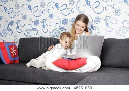 young woman with baby working with laptop at home