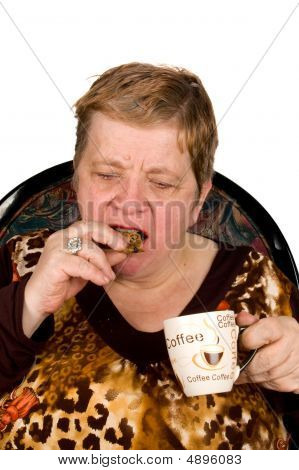 Elderly Woman Is Drinking Coffee And Eating A Cookie