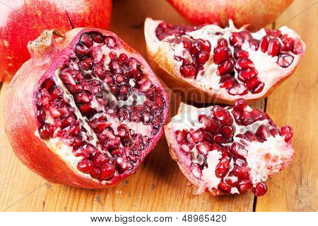 Cut Open Pomegranate On Wooden Cutting Board