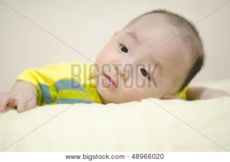 Asian infant thinging lying on the bed
