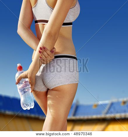 sports woman who holds bottle of water at stadium